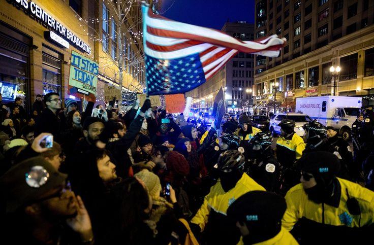 Οι διαδηλωτές κρατώντας την Αμερικανική σημαία ανάποδα διαμαρτύρονται στο Σικάγο για την ατιμωρησία λευκών αστυνομικών για τις δολοφονίες άοπλων πολιτών αφρικανικής καταγωγής.