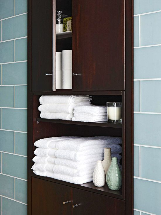 built in wall cabinet -(Note also blue glass tiles)  A custom built-in has the look of a cabinet without taking up any floor space, and it offers ample storage for towels, toiletries, and other necessities. This cabinet is recessed into the wall, providing the bathroom with a low-maintenance, stylish storage boost.  If move toilet to back wall, might have room for more cabinet space at end.