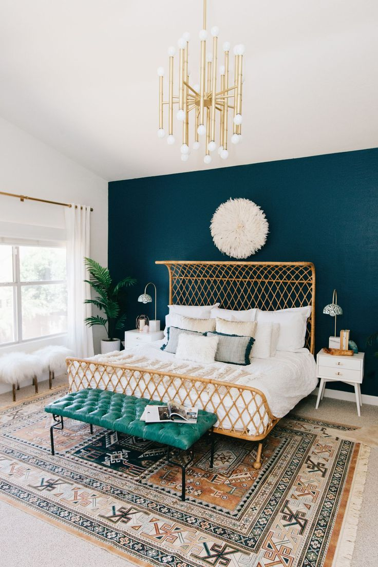 rattan king size bed against a teal wall with a boho rug and teal tufted leather bench makes for a cozy and eclectic master bedroom.