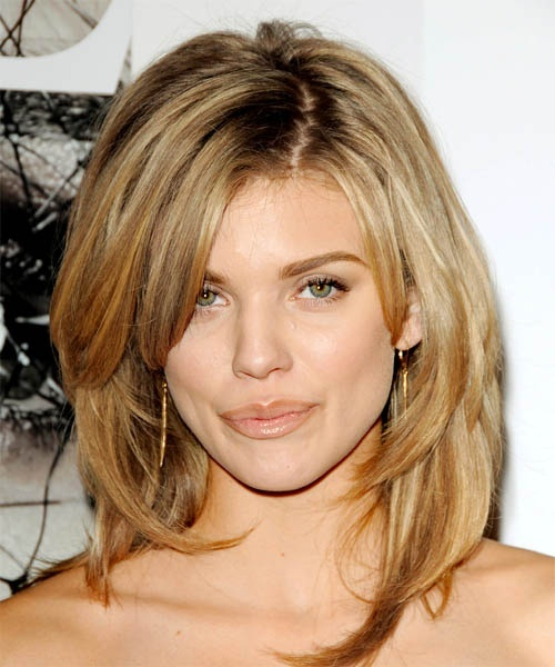 Medium length haircut with shaggy layers, cut through the back, that creat body and volume from her mid-lengths to her ends. hair