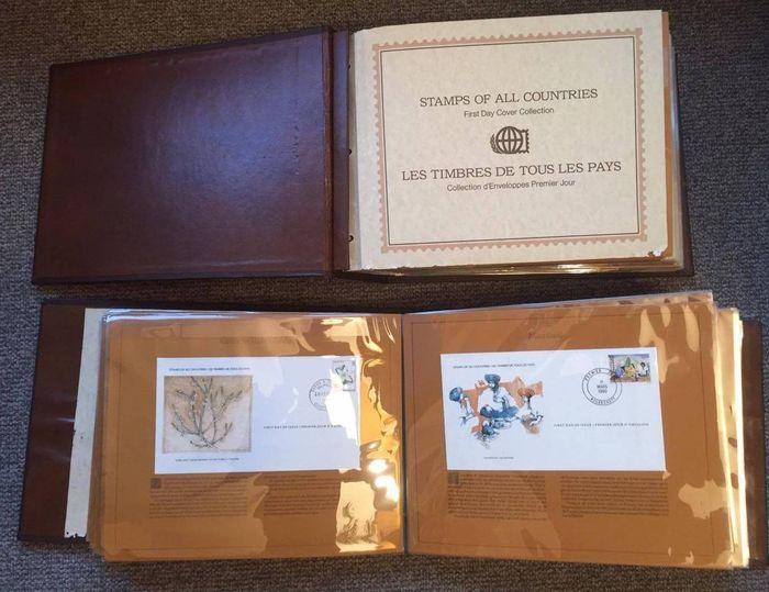 Wereld 1977/1984 - Partij 224 FDC 'Stamps of all countries' - Vol. 1 & 2  Twee maal 'Stamps of all countrie's' collectie uitgegeven door de international society of postmasters. Elke enveloppe heeft op de achterkant een certificate of authenticity geprint staan. De enveloppen komen elk met een uitleg op dik karton en zitten met twee stuks (ruggen naar elkaar) in een bladzijde. Leer gebonden boeken in zeer goede staat compleetIn totaal gaat het om 224 eerste dags enveloppen uit verschillende…