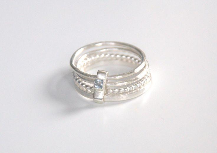 Vier zilveren ringen verbonden door een zilveren ovalen stukje afgewerkt met een blauwe aquamarijn.
