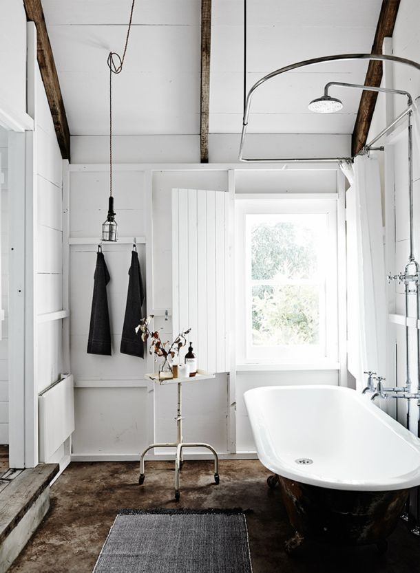 The bathroom also emits a sense of Scandinavian chic design with a gorgeous freestanding vintage ball and claw bathtub. Exposed wooden beams bring warmth and character to this area and white wood, against rustic floors creates charm here in neutral and natural shades.