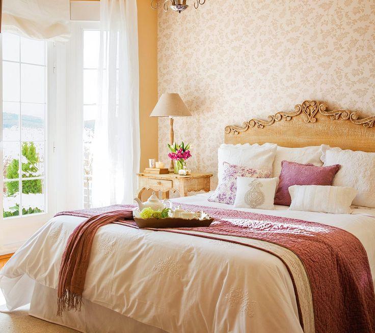 Dormitorio con cabecero de madera tallada y papel pintado en la pared. Fresco y femenino en beige y malva