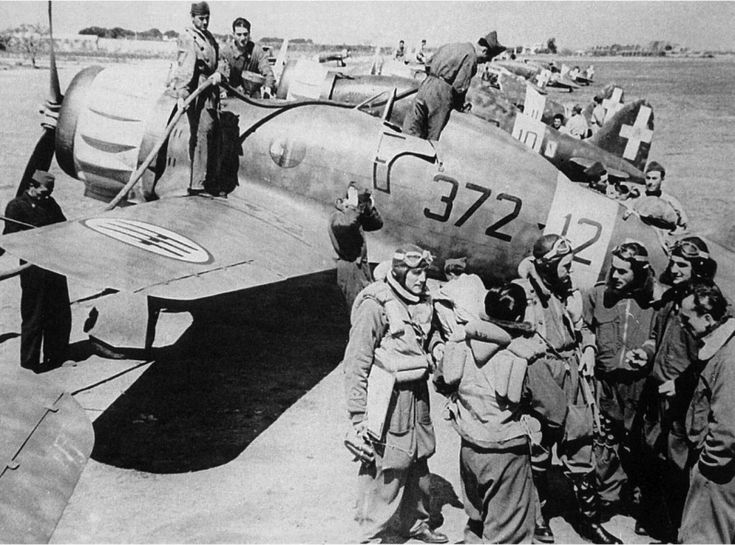 Italian pilots of 372 Squadron at his fighter Macchi C.200 «Saetta» at the airport