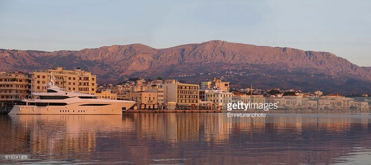 the port of chios has a long promenade and is deep enough for large size cruisers to dock. on a calm autumn day,this image was formed at sunrise with the reflections of buildings and the hills at the background.