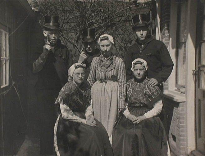 Drie mannen en drie vrouwen poseren in historische Scheveningse dracht. Met Klara Hendrika Grootveld (midden), Hanny Roeleveld (links van haar), (Atie?) Knoester (rechts van haar). De foto is gemaakt bij gelegenheid van de 50e verjaardag van koningin Wilhelmina. Op 30 augustus en 1 september 1930 trok 's avonds een lichtstoet door Den Haag en Scheveningen, waarbij onder meer een Scheveningse bruiloft in 1830 en 1930 werd uitgebeeld. ca 1930 #ZuidHolland #Scheveningen