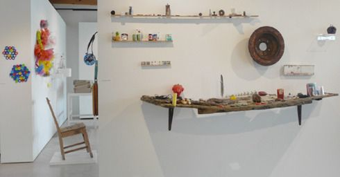 """Left > Right: Fused plastic by Sarah Lenton, Wall Flowers by Christine Butler, + Yellow plastic with wire and other objects on the wall are by Lynsie Austin, Chair with metal protusions by Beverley Cox, """"Collections"""" the objects + shelving on the front wall are by Liz McAuliffe."""