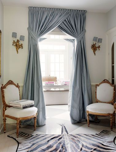 Elevated tie backs and overlapped drapes can dramatize a room's height.