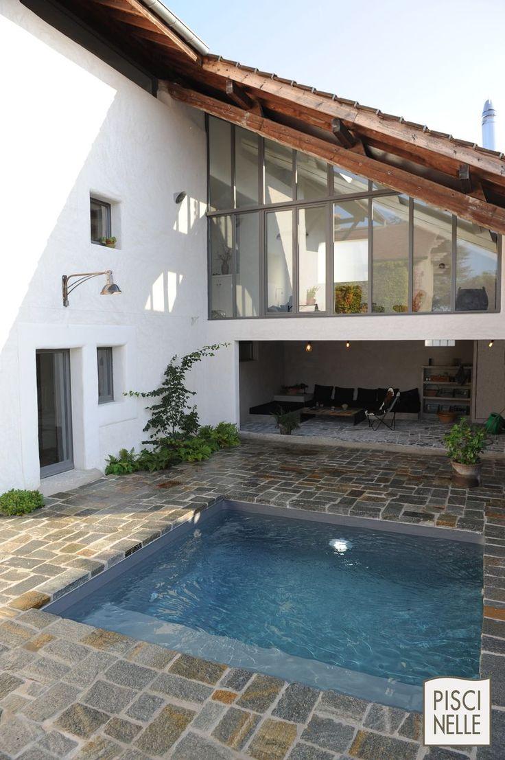 Petite piscine dans une cour intérieur avec abords en pierre naturelle.