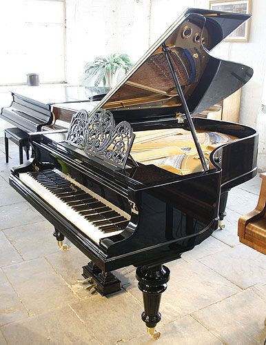 An 1895,Bluthner grand piano with a polished, black case and ornate music desk.  #bluthner