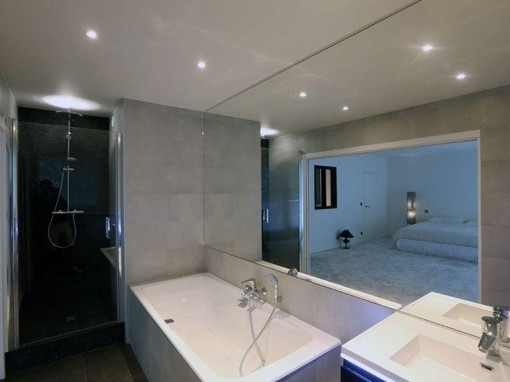 Un grand miroir, d'un seul tenant, recouvre le mur principal. La douche est en partie recouverte de mosaïques de marbre noires. Le carrelage est anthracite au sol (60x60cm) et gris au murs(30x60 cm). Très lumineuse, elle est ouverte vers l'extérieur grâce à une fenêtre et sur le reste de l'appartement via une porte double encastrée.  - Modern and design bathroom. A large mirror covers the main wall. The shower is covered with black mosaics. - Xavier Lemoine Architecte d'Intérieur Paris 17-