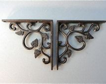 a pair of small cast iron antique style leaf brackets