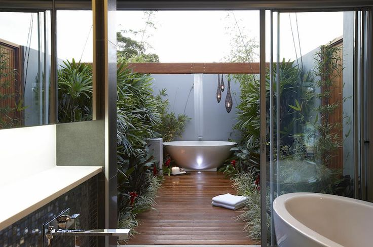 Wooden flooring is used for this stunning tropical bathroom and plants around the path that leads to the bathtub. ➤To see more Luxury Bathroom ideas visit us at www.luxurybathrooms.eu #luxurybathrooms #homedecorideas #bathroomideas @BathroomsLuxury