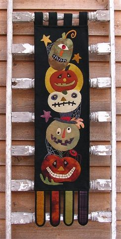 """Gourdy's Gang, 10"""" x 40"""" wool applique wall hanging by Threads That Bind"""