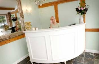 chic retail check out counters | Curved Reception Desk with Cream faux leather padded front