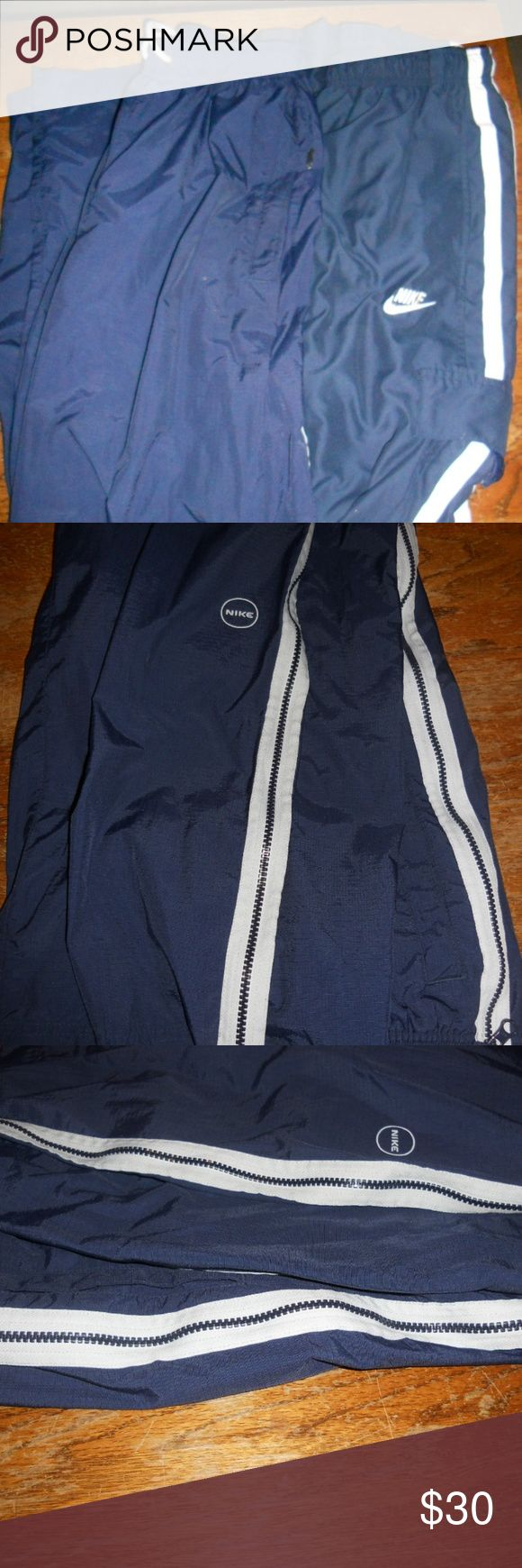 2 NIKE Men's Blue Athletic Pants Size Medium 2 NIKE Men's Draw-string Blue Track Running Pants Zippered Leg Medium One pair is 100% Nylon and has zippers the length of both legs. The other pair is 100% polyester. Both pairs are a size medium and have drawstrings. Both are in excellent condition. Nike Pants Sweatpants & Joggers