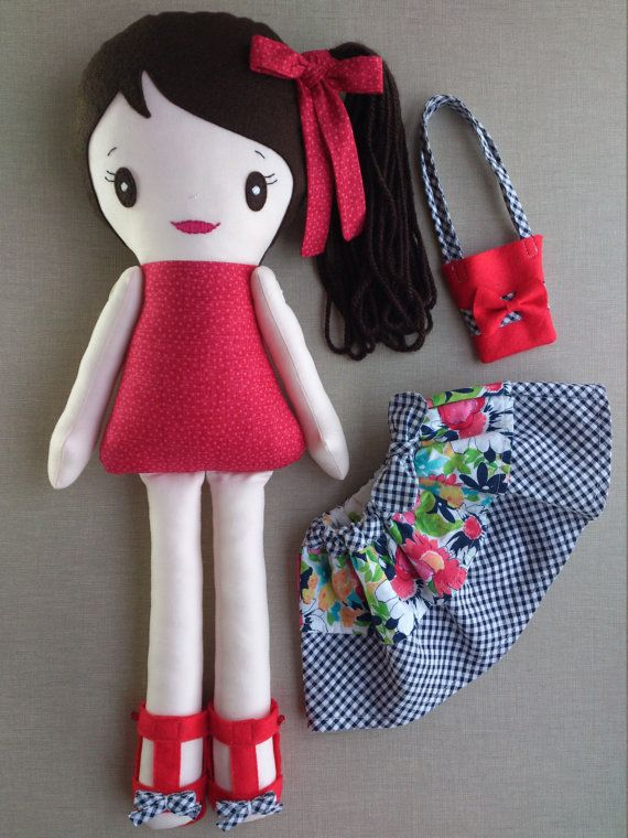 This is Daniela, one of a kind and rebel handmade rag doll. She measures 20 and she is made with wool blend felt, 100% cotton fabric and wool. She wears a red blouse, a skirt with a blue bow in the waist, a pair of red sandals and a little tote bag. In her ponytail, she wears a red bow. Her face has been hand-embroidered and details have been made with care. Her arms can be moved. Cloths and shoes can be removed and her body is stuffed with Polyfill, so she is more soft. Hand wash only. Not…