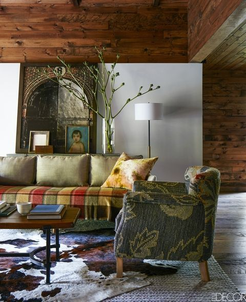 Amanda Seyfried's rustic Catskills retreat is a study in cozy modernism. The living area in the barn that now serves as guest quarters features a sofa by West Elm, the wool rug is by Restoration Hardware, the flooring is reclaimed oak, and the wall is painted in Benjamin Moore's White Dove; the photograph is by Sarah Bailey.