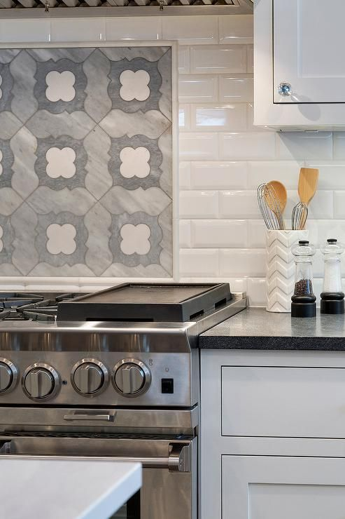 Gorgeous quatrefoil mosaic cooktop tiles framed by white beveled subway tiles serve as the backsplash for a stainless steel range positioned beside flat faced white drawer and white shaker cabinets topped with a black granite countertop and fitted with round glass pulls.