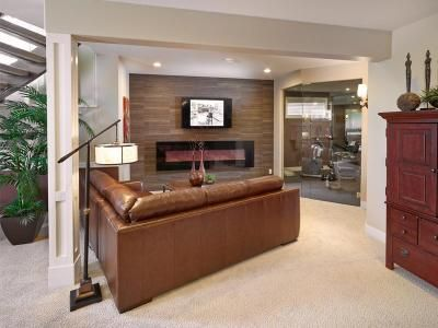 This basement living room, has a lovely neutral stone/tile feature wall around linear fireplace. The Christina model by Kimberley Homes, Edmonton, Alberta