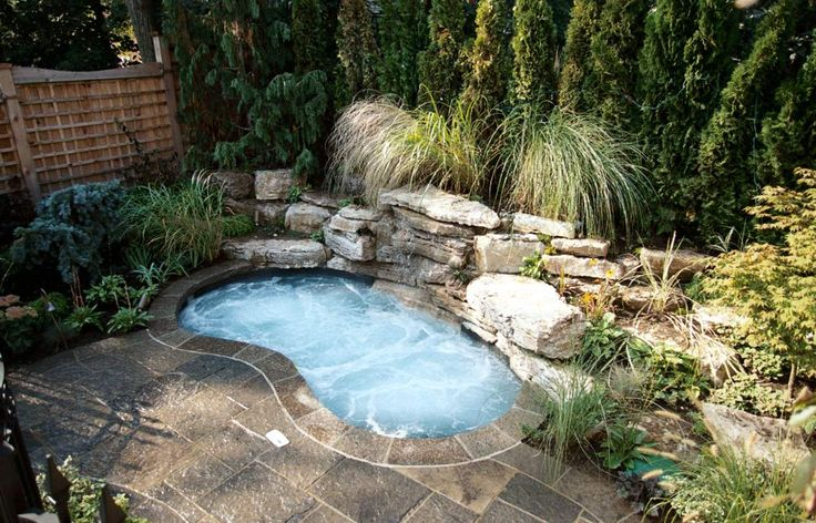 A little 'oasis' was created in this compact urban yard.  The plunge-pool/spa with black slate interior and integrated rock feature, has a waterfall surrounded by the lush plantings. The deck is natural square-cut flagstone set on a concrete base. A natural cedar hedge and custom cedar side screens provide privacy. With equipment in the garage, insulated plumbing lines and a custom cover allow for year round use. (8 x 13, kidney shape)