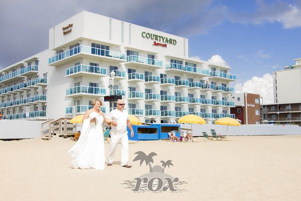 Beach Bride is escorted to the beach during her wedding processional in front of the Courtyard Marriott Hotel in Ocean City, MD - image by Rox Beach Weddings:  https://www.roxbeachweddings.com/