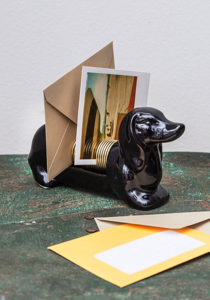 A dachshund letter organizer is on a desk and storing lan envelope and photograph.