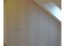 A run of our handmade wardrobes fitted under the eaves, with plenty of space for hanging clothes tidily out of sight.