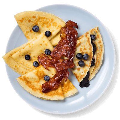 Hjemmelagede pannekaker er lett å røre sammen. Fyll dem med sprøstekt bacon og blåbærsyltetøy. Oppskrift på pannekaker.