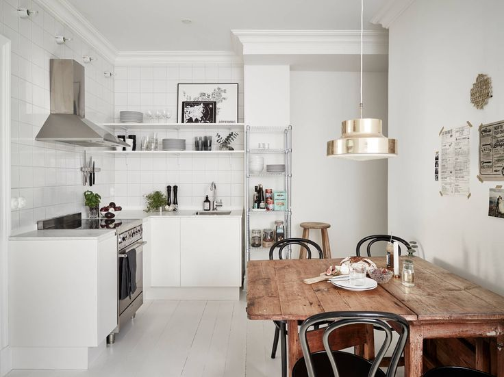 Scandinavian kitchen, rustic wooden table, Thonet chairs and brass pendant
