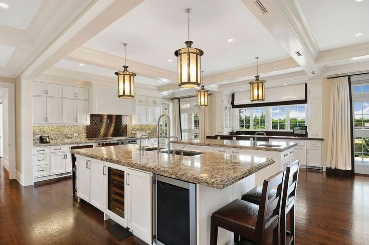 This large kitchen features crisp white walls and ceilings, contrasted by a rich stained wood floor. Do you like the pendant lantern lighting?  Source: https://www.zillow.com/digs/Home-Stratosphere-boards/Luxury-Kitchens/
