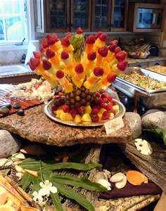 Hawaiian Luau food presentation. Stick skewers of fruit in pineapple, another dessert and a centerpiece too.