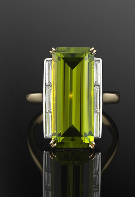 18K Yellow Gold Peridot and Diamond Ring. A long emerald cut peridot weighing approximately 4 carats is accented to either side with a row of baguette diamonds in an 18 karat yellow gold mounting, circa 1970s like the setting change to center stone