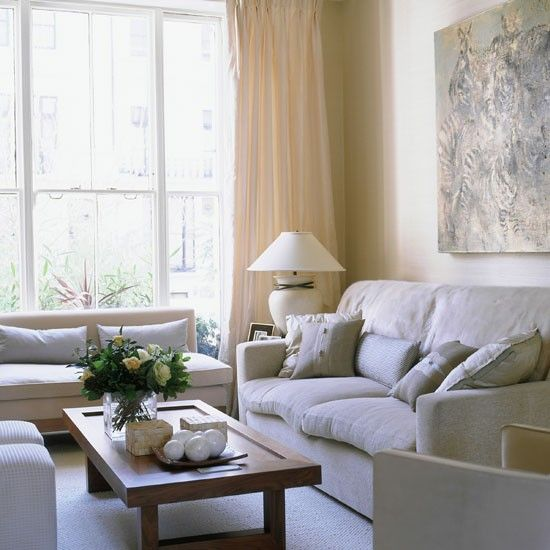 This living room has a light tan couch, light beige curtains, a light brown painting above the couch, and a light brown table. The room looks sleek and clean but is also boring. It has not tonal variation and nothing to carry your eye around the room. The amount of light coming into the room also adds to the brightness and washed out look.