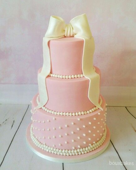 Tiered pink and pearl wedding cake with edible fondant bow cake topper