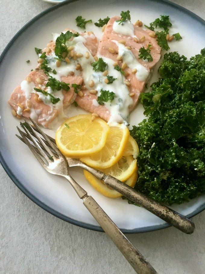 Lemon Baked Salmon with Pine Nuts and Mint Yogurt Sauce brings together my favorite Mediterranean flavors to create a flavorful, nutritious dinner that is ready in under 30 minutes.  The lemon baked salmon is topped with toasted pine nuts and a minty yogurt sauce. // A Cedar Spoon