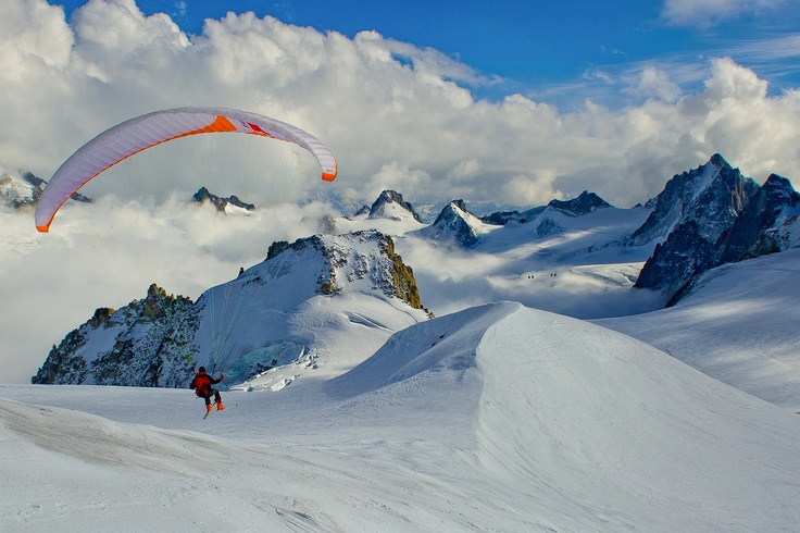 A paraglider, as seen from the Glacier Blanche, next to Aiguille du Midi, just few seconds after take off. Photograph taken during winter climbing session in Mont Blanc Massif, Chamonix, France.
