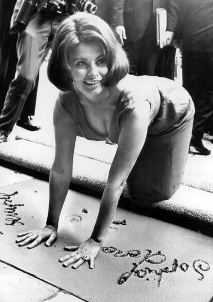 Sophia Loren places her handprints in cement at Grauman's Chinese Theatre. July, 1962