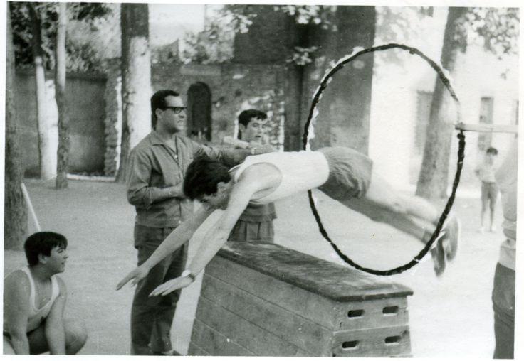 Niños del Colegio Episcopal realizando una exhibición de gimnasia en la que saltan un potro y un aro de fuego. | Archivo de la Imagen de Castilla La Mancha, Public Domain