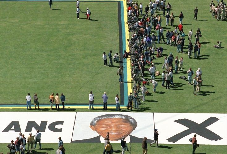 Portrait of Nelson Mandela painted on the grass of Soweto's largest football stadium during an election rally, 1994. Courtesy the artist. © Graeme Williams.