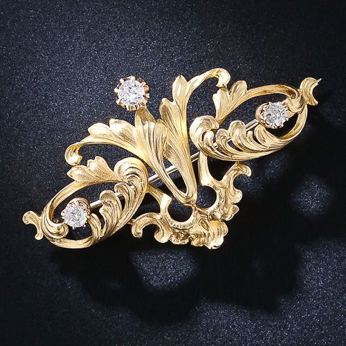 An exquisitely designed and rendered Art Nouveau brooch, sculpted in rich 22 karat yellow gold, shimmers with flowing leaves and feathery plumes enlivened with a sparkling trio of old mine-cut diamonds. 2 inches by 1 3/16 inches, circa 1890 - 1910.