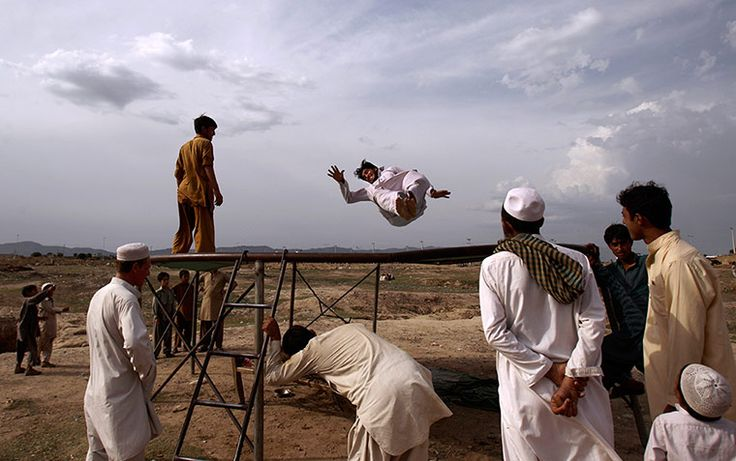 when grown men get to play Leap of faith: a man who fled his village due to fighting between security forces and militants in Pakistan's tribal area of Bajur enjoys jumping on a trampoline at a makeshift entertainment park on the outskirts of Islamabad Photograph: Muhammed Muheisen/A