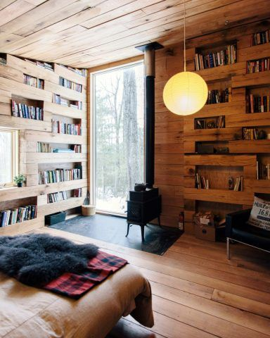 As tábuas de madeira que revestem as paredes da cabana são intercaladas para formar as prateleiras de livros