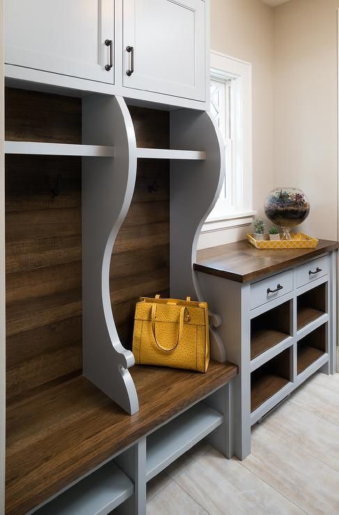 Yellow and gray mudroom features gray open lockers and bench next to a message…