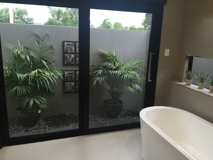 Tropical Bathroom view with an external privacy wall.....