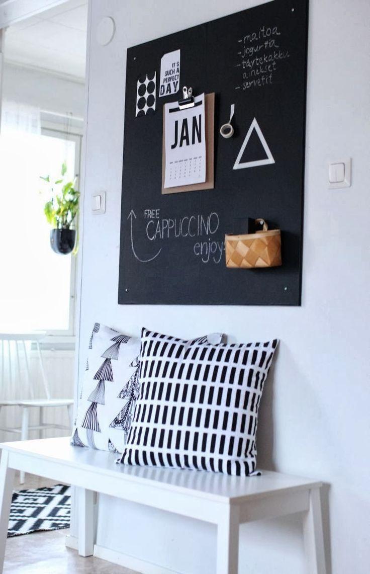 Banco de IKEA, tablero pintado con pintura pizarra negra para colocar imágenes y unos bonitos cojines. Una sencilla entrada de estilo en blanco y negro minimal. DECODIY✖️