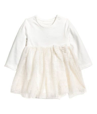 White. Dress with attached bodysuit in soft jersey and a tulle skirt. Bodysuit with scalloped neckline, long sleeves, and snap fasteners on shoulders and at