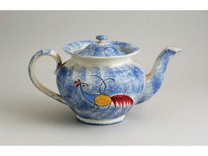 An American blue spatter teapot, with double-sided blue, yellow and red peafowl