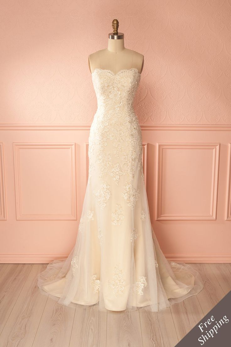 Eugenia #Boutique1861 / This delightful wedding dress will make your heart skip a beat! With embroidered lace tulle overlapping its satin champagne tissue, this mermaid dress also has a long train as well as a removable ornate crystal belt. The bodice has padded cups, boning and a zipper hidden under a long string of decorative buttons. Wear your hair in an up-do to show off the fabulous back and neckline!
